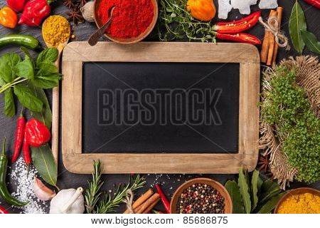 Various spices on black stone with blank blackboard, shot from aerial view