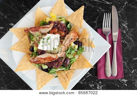 Meal of nachos with grilled chicken fillets