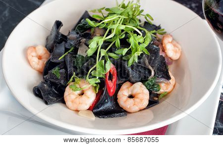 Plate of squid ink pasta and prawns
