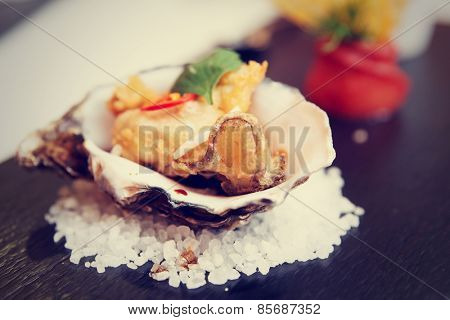Tempura fried oyster in shell, delicious appetizer, toned image