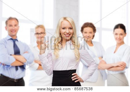 business, team work and people concept - smiling businesswoman, student or secretary over group of colleagues in office background
