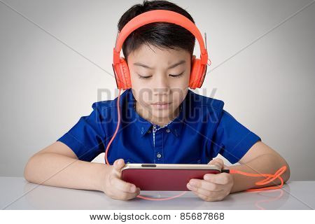 Asian Boy Ware Headphone And Playing The Cell Phone