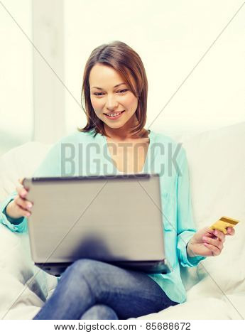 home, technology, online shopping and internet concept - smiling woman sitting on the couch with laptop computer at home