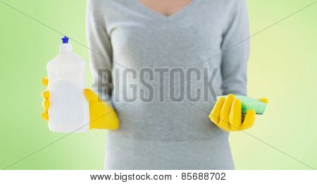 people, housework, washing-up and housekeeping concept - close up of woman holding sponge and cleanser bottle over green background