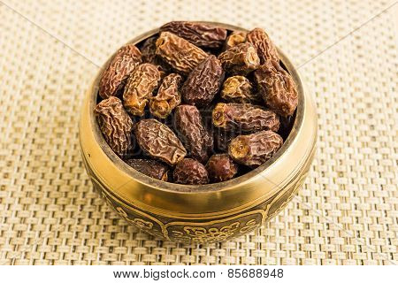 Macro view of dried dates kept in a bowl under a plain background