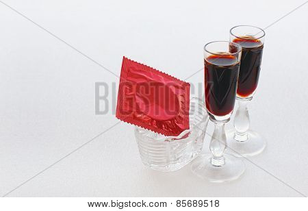 Red Condom In A Small Vase And Two Glasses With A Dark Drink