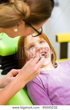 Dentist practicing with child in dental surgery