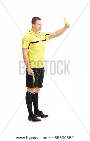 Full length portrait of a football referee showing a yellow card isolated on white background