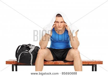 Worried male sportsman sitting on a bench isolated on white background