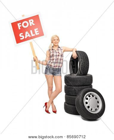 Full length portrait of a young woman standing next to a pile of tires and holding a red for sale sign isolated on white background
