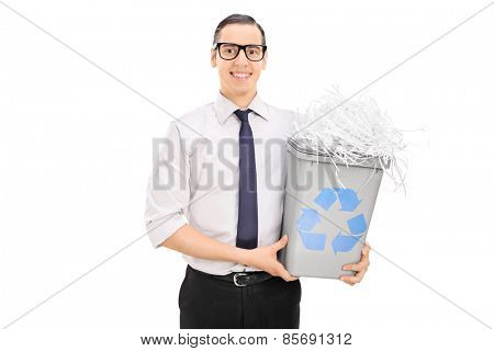 Young man holding a recycle bin full of shredded paper isolated on white background
