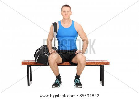 Studio shot of a male athlete in sportswear sitting on a wooden bench and carrying a black sports bag isolated on white background