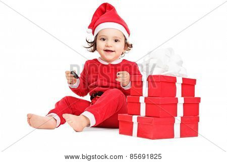 Cute little girl sitting by a pile of Christmas gifts isolated on white background