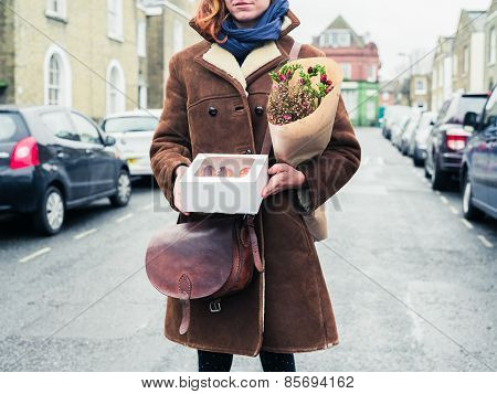 Young Woman Standing In Street With Cake And Flowers