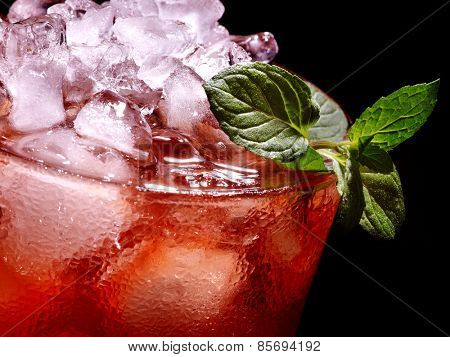 Cold red drink  with raspberry and mint leaf on black background.