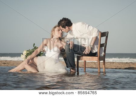 beautiful in love couple sitting on beach at water's edge