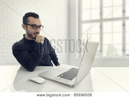 Happy man working on laptop in a his office