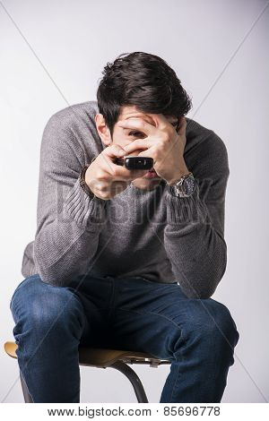 Young Man With Remote Control, Covering His Eyes Scared
