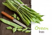 foto of phaseolus  - Piattoni green beans with knife on the old wooden table - JPG