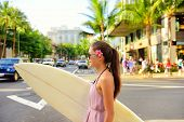 stock photo of waikiki  - Surfer woman walking in city with surfboard to go surfing - JPG