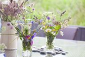 image of vase flowers  - picked wild flowers with colorful flowers in a vase and glasses on a table decorated