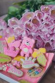 stock photo of biscuits  - on the table colored different figures of biscuits and a bouquet of tulips - JPG