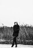 stock photo of cold-weather  - Fashion woman wearing a winter coat and fur cap and she posing front of the reeds cold rainy weather full length black and white image - JPG