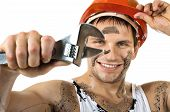 image of turn-up  - happy worker man dirty in safety helmet with big wrench in hands turn on and smile on white background isolated - JPG
