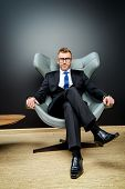 stock photo of mature men  - Imposing mature man in elegant suit sitting on a leather chair in a modern luxurious interior - JPG