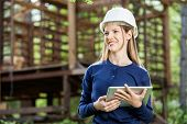 image of timber  - Happy female architect holding digital tablet against incomplete timber cabin at construction site - JPG
