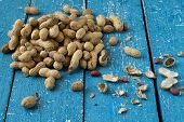 stock photo of groundnut  - Pods shells and groundnut seeds on a blue wooden background - JPG