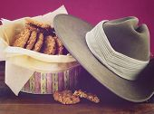stock photo of biscuits  - Australian Anzac biscuits in vintage biscuit tin with army soldier slouch hat and applied retro vintage style filters - JPG