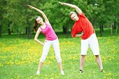 picture of physical exercise  - fitness man and woman doing physical stretching exercises during outdoors sport training - JPG