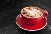 picture of sprinkling  - A red cup and saucer holds a cappuccino coffee with a sprinkling of chocolate - JPG