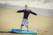 stock photo of boggy  - Happy Young boy having fun at the beach on vacation - JPG