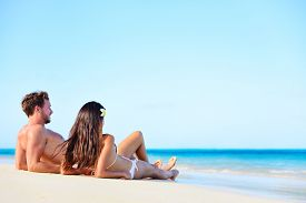 stock photo of under sea  - Beach vacation couple relaxing tanning in summer - JPG