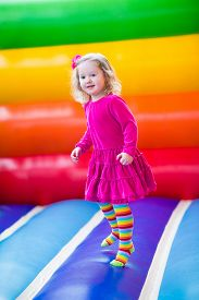 picture of inflatable slide  - Cute funny preschool little girl in a colorful dress playing jumping and bouncing in an inflatable castle having fun at a children birthday party on a kids playground in summer - JPG