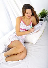 picture of nighties  - young attractive and beautiful woman in nightgown lying on bed at bedroom writing diary with pen in relax looking tranquil and happy in American lifestyle concept - JPG