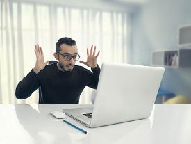 image of crappie  - Man Shocked Reading Message on Computer in Office  - JPG