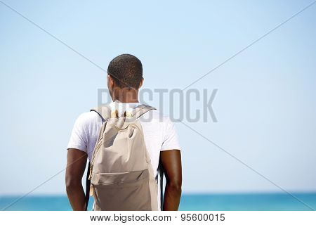 Man Standing With Backpack By The Sea