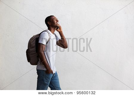 Happy Student Walking And Talking On Mobile Phone