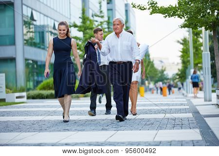 Business team walking together on a way in summer
