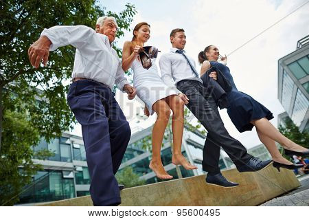 Group of business people jumping together over obstacle outdoors