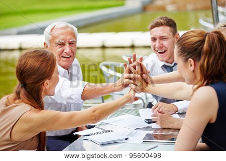 Successful business people doing high five in a meeting for motivation