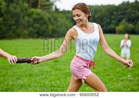 Young happy woman running a relay race in a park