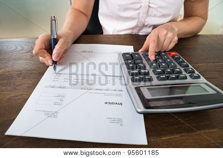 Businesswoman Calculating Tax At Desk