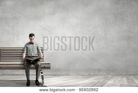 Young man in bow tie sitting with book in hands