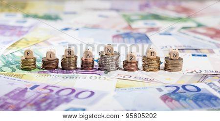 German Word Finanzen On Coin Stacks, Cash Background