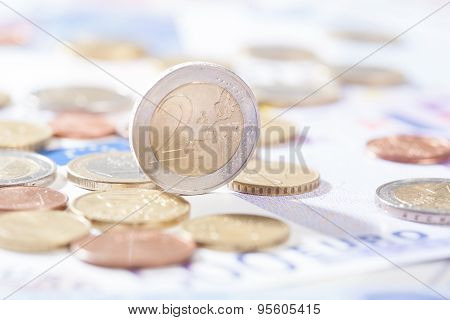 Two Euro Standing On Bank Notes And Coins