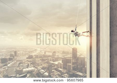 Determined businesswoman climbing building with help of rope